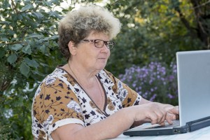 elderly woman working on  computer in the garden